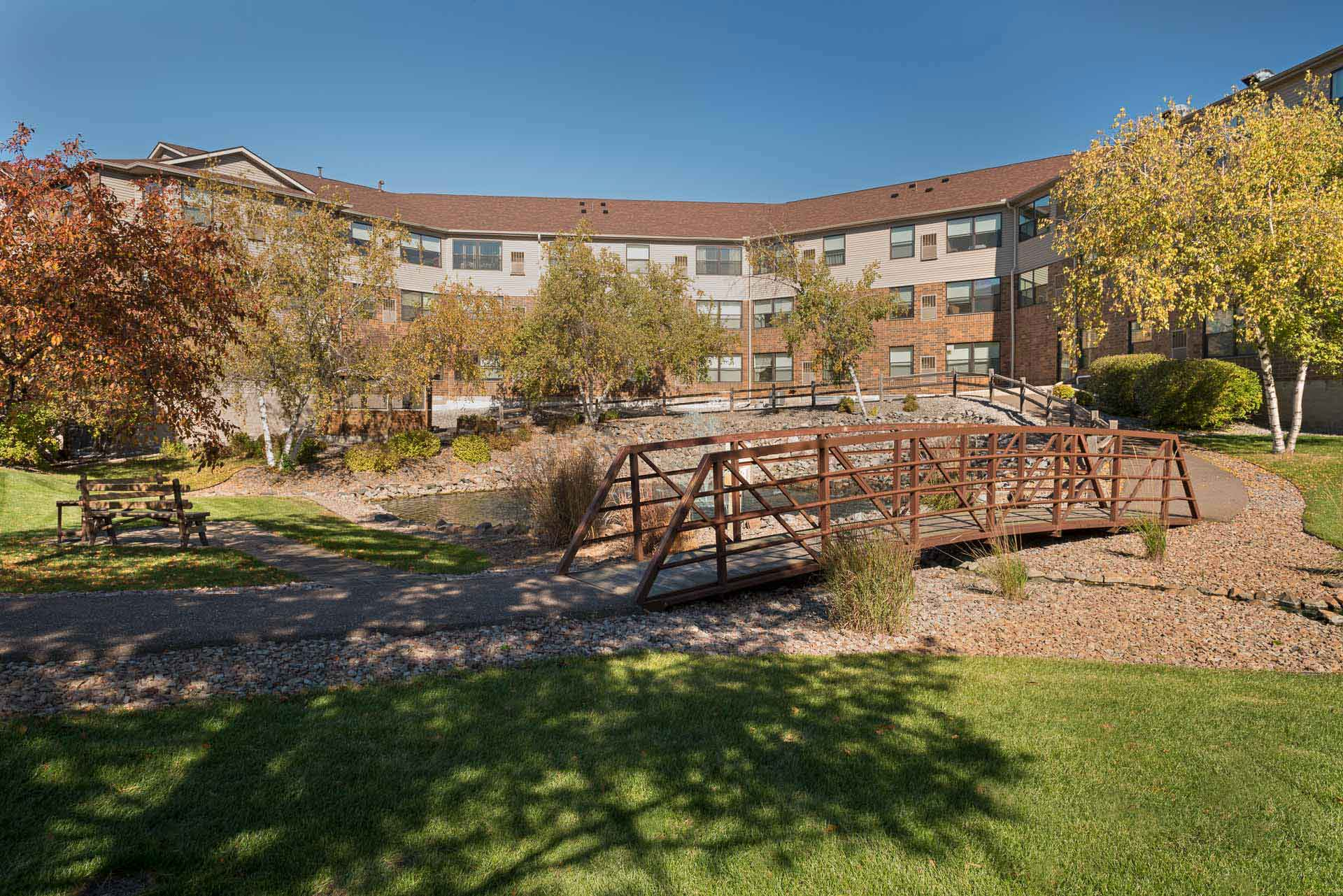 Back of Epiphany Senior Housing building with a walking path and bridge
